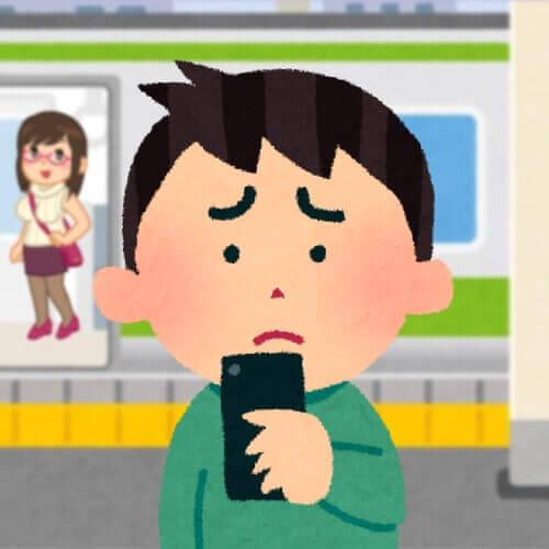 困った表情でスマホを持つ男性
